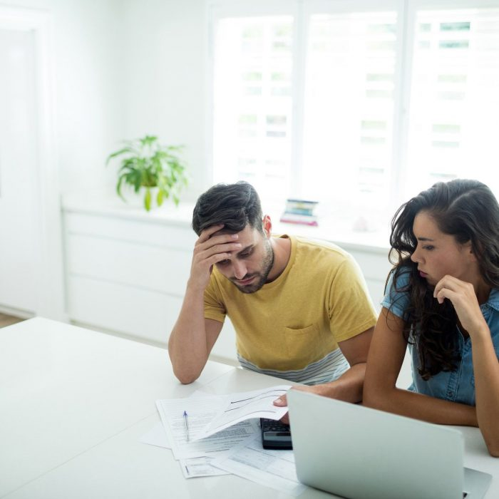 Worried couple calculating their invoices with laptop in the kitchen
